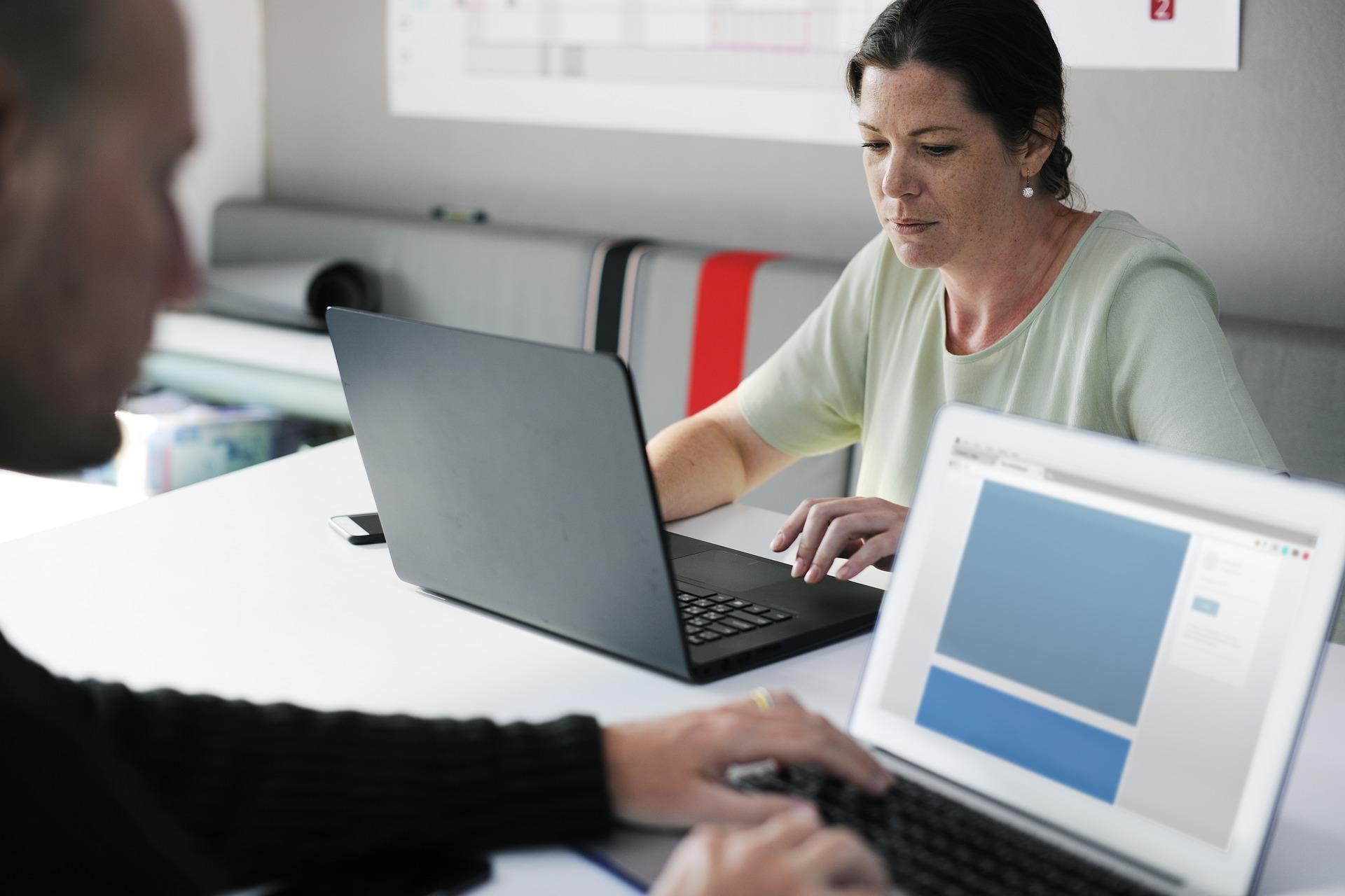 Ihmisiä työskentelemässä tietokoneilla